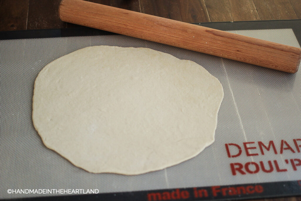 pizza dough sitting on roulpat mat with rolling pin