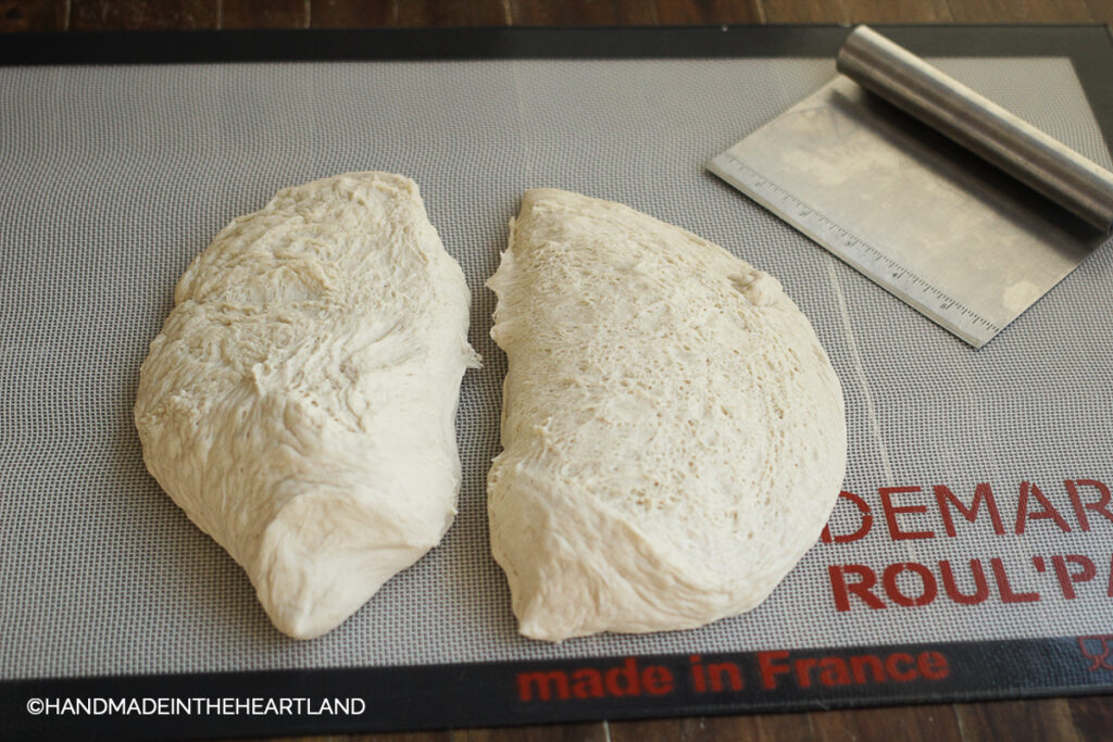 pizza dough sitting on a roul'pat silicone counter mat with silver metal pastry cutter