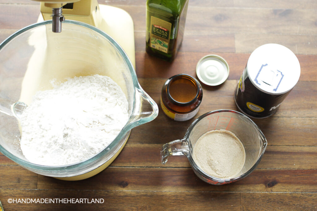 kitchen aid mixer with flour in the bowl with olive oil, yeast, salt and measuring cups sitting next to mixer