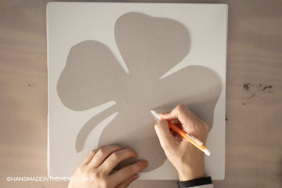 tracing chipboard shamrock onto white canvas