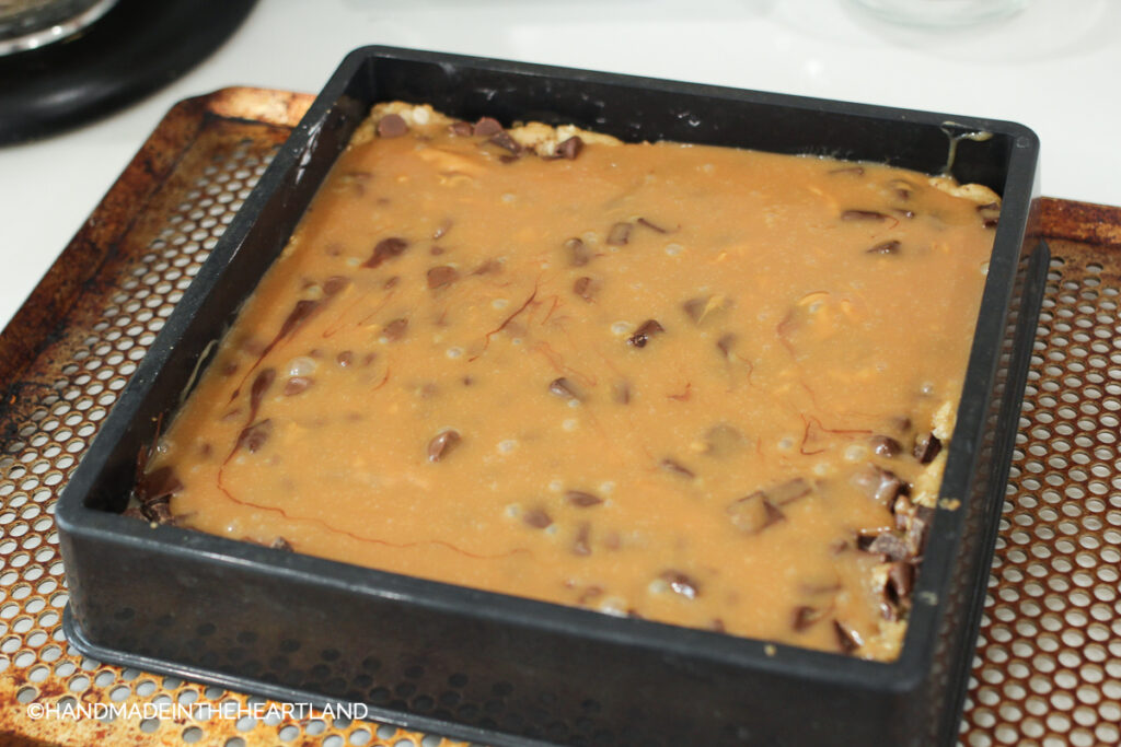 adding caramel sauce and chocolate chips to pre baked cookie crust