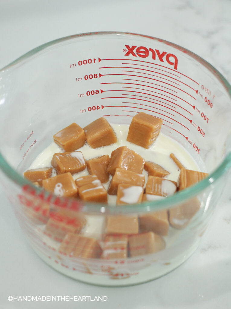 caramel candies and heavy whipping cream in a pyrex measuring cup, ready to melt to make caramel sauce