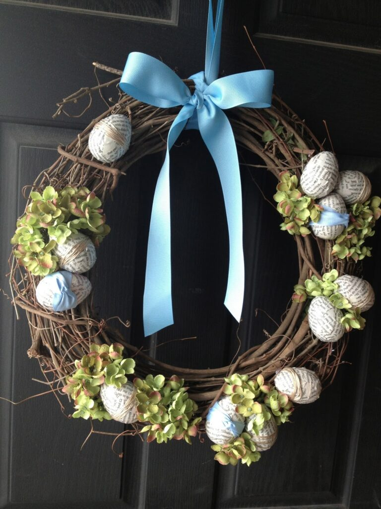 Easter wreath hanging on a black front door with Easter eggs, hydrangeas and ribbon