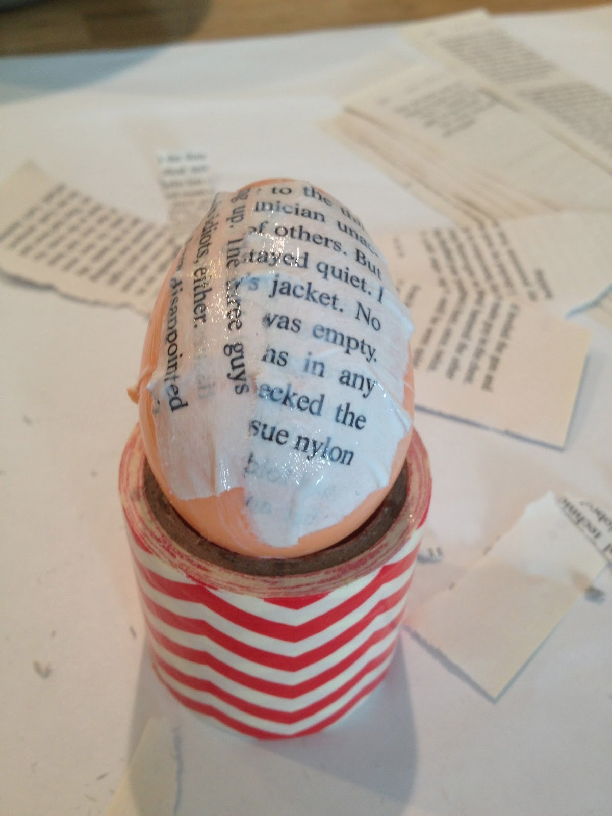In process decoupage of applying pieces of book pages to a plastic easter egg